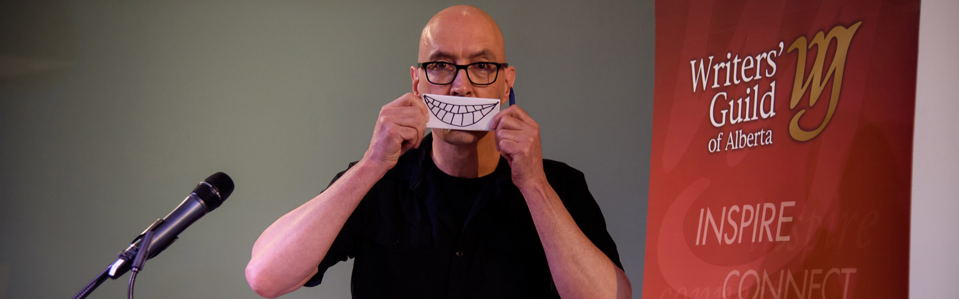 Dr. Patrick Finn poses holding a smile drawn on a piece of paper in front of his mouth.
